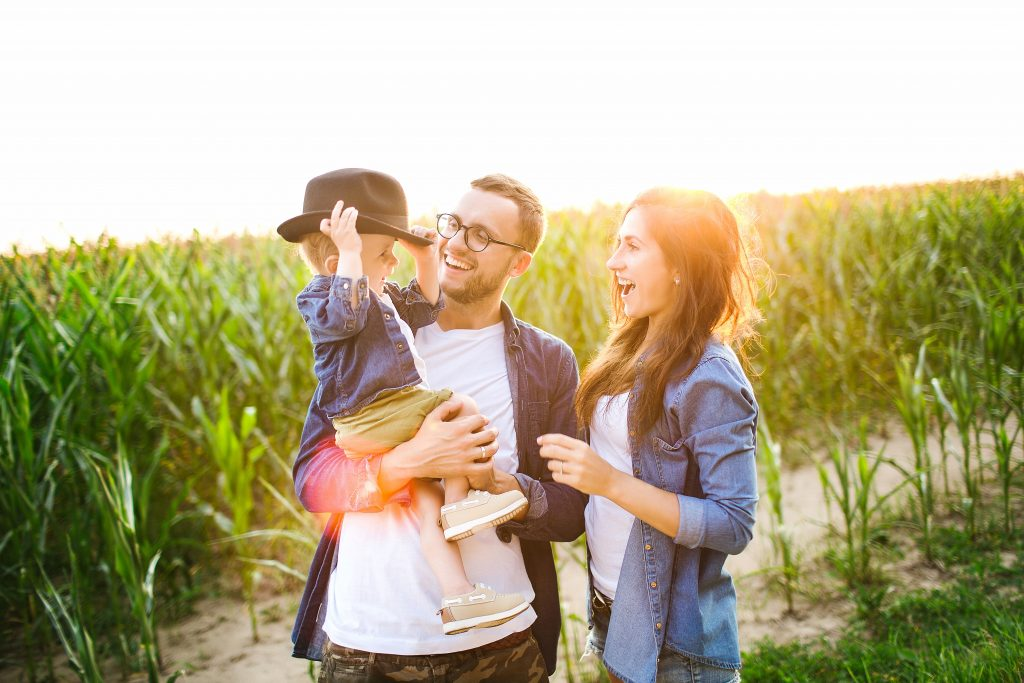 Young hipster father in glasses, mother holding cute baby in summer cornfield