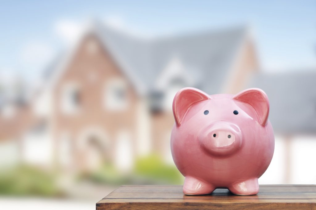 Saving to buy a house, real estate or home savings, piggy bank in front of property